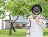 Man or cook in apron hiding face behind frying pan Royalty Free Stock Photo