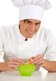 Man cook with broken egg above green bowl Stock Photo