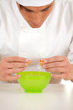 Man cook with broken egg above green bowl Royalty Free Stock Image