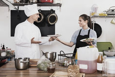 Man cook giving to waitress ready to serve salad Royalty Free Stock Images