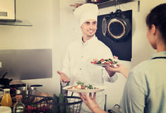 Man cook giving to waitress ready to serve salad Royalty Free Stock Photos