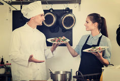 Man cook giving to waitress ready to serve salad Stock Image