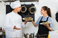 Man cook giving to waitress ready to serve salad Stock Images