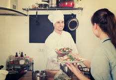 Man cook giving to waitress ready to serve salad Stock Photo