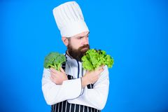 Man cook hat apron hold broccoli and lettuce. Vegan recipe concept. Buy fresh vegetables grocery store. Vegan restaurant. Hipster chief chef vegan cafe. Health stock image