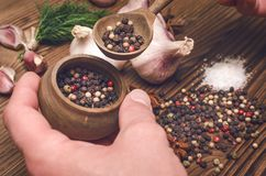 Man holding in hands a pot and spoon with pepper peas. stock image