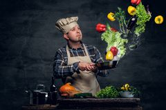 Free Man Cook Holds A Pan With Vegetables Flying In The  Air. Royalty Free Stock Photography - 115663257
