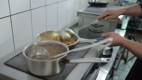 The man cook the indiand dishes in the restaurant. The man cook the indian dishes in the restaurant. Chef mix the spaghetti with scoop and adds the green spices stock footage