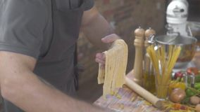 Man cook making fresh italian pasta on home kitchen on food background. Chef cook putting handmade raw pasta on table by stock video footage