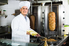 Man cook making kebab dish on kitchen in fast food restaurant Stock Photo