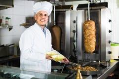 Man cook making kebab dish on kitchen in fast food restaurant. Smiling spanish  mature man cook making kebab dish on kitchen in fast food restaurant Stock Photo