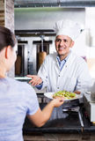 Man cook serving fresh kebab dish to customer on counter in fast Stock Images