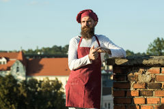 Man cook standing with rough. Handsome man cook chef hipster with long beard in red hat and apron uniform holding dough in hands standing leaning on brick wall royalty free stock images
