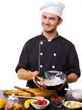 A man, a cook, stands in the kitchen showing a batter with strawberries. Stock Images