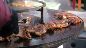 The man cook turns meat on the grill. Men cook grilled meat. Close-up of the chef`s hands that flip over raw chicken. Meat on the round barbecue. Street food stock video footage