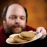 Man with Cookie. Overweight middle aged man with cookies Stock Photos