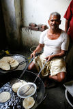 Man cooking. DELHI - FEBRUARY 26. Man cooking chapatis in oil to make Puri on February 26, 2008 in Dehli, India. Chapatis are the staple diet of all Indians stock image