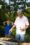Man cooking on barbeque by son (9-11) with hands on head, smiling Royalty Free Stock Photography