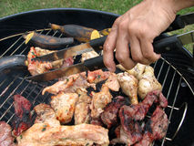Man Cooking BBQ. A man cooking bbq during a hot summer day Stock Photo