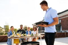 Man cooking on bbq and friends at rooftop party royalty free stock photography