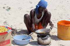 Man cooking on the beach with a simple makeshift kitchen Stock Images