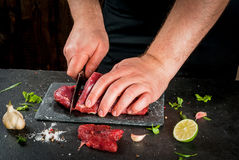 Man cooking beef meat. Preparation of dinner. Cooking, processing of meat beef, tenderloin. Person male hands cuts a piece of meat into steaks pieces. Black Stock Images