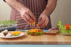 Man cooking big sandwich in home kitchen Stock Photography