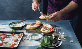 Man cooking bruschetta with baked tomato, cheese and garlic Royalty Free Stock Image
