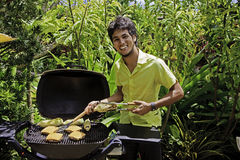 Man cooking burgers on barbecue Stock Photo