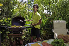 Man cooking burgers on barbecue Royalty Free Stock Images