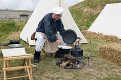 Man cooking on campfire Stock Images