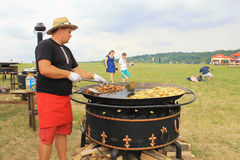 Man cooking crisp potato on the huge grill outdoor pan, Pirogov Royalty Free Stock Image