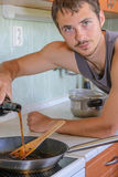Man cooking currant sauce. Young Man in the kitchen cooking currant sauce Stock Photos