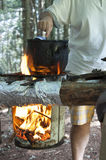 Man cooking dinner on campfire. A man cooking food in pot on fire at camping place Stock Photos