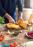 Man cooking dish of squash stuffed with rice and cranberries Royalty Free Stock Photo
