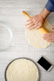 Man cooking dough for two pizzas on the kitchen Royalty Free Stock Images