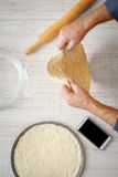 Man cooking dough for two pizzas on the table Royalty Free Stock Images