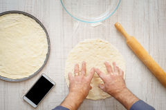 Man cooking dough for two pizzas on the wooden table Royalty Free Stock Photos