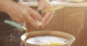 Man Cooking Eggs on a Frying Pan for Breakfast Adding Salt and Pepper in the Kitchen with Sunshine Shot on Red Camera