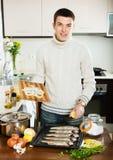 Man cooking  fish  in baking sheet at home Stock Photo