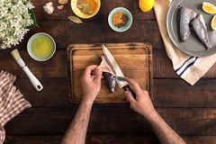 Man cooking fish on a rustic wooden table. Healthy food and diet concept, top view Royalty Free Stock Image