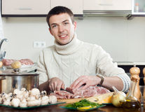 Man cooking french-style meat. Adding grating cheese in roastin Royalty Free Stock Photography