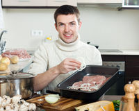 Man cooking french-style meat. Adding onion  in roasting pan Royalty Free Stock Images