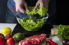 Man is preparing green salad of romaine lettuce. Healthy food concept stock image