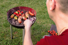 Man cooking at grill with various delicious barbecue outdoor, selective focus Royalty Free Stock Photo