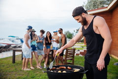 Man cooking grilled sauseges and vegetables on barbeque party Stock Image