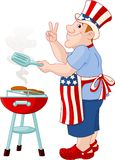 Man cooking A Hamburger. Funny Man with Uncle Sam Hat cooking A Hamburgers On A Barbecue Bbq Grill Stock Photo