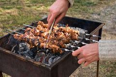 Man cooking, only hands, he is cutting meat or steak for a dish. Delicious grilled meat on grill. Barbecue weekend. Selective focu Stock Photography