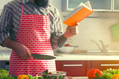Man cooking healthy salad and reading book Royalty Free Stock Images