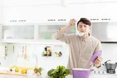 Man cooking at home in kitchen. Young man cooking at home in kitchen Royalty Free Stock Photography